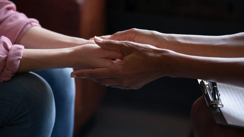 Counsellor psychologist holding hands provide mental help to patient